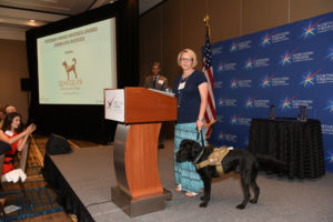 Semper K9 Board member Tisa Newhouse, with service dog Vinny accepts the 2017 Distinguished Service Award